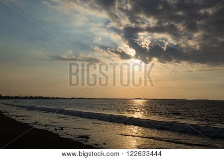 Dramatic sunset with clouds on the ocean coast. Sunny track on water. Sun rays in the clouds. Fiji.