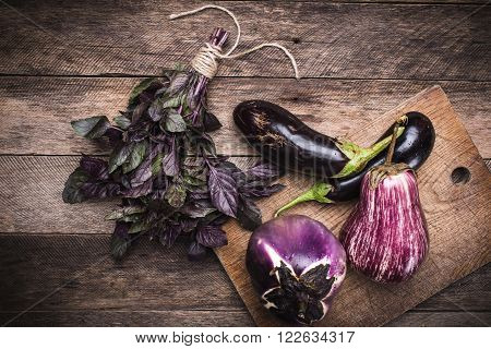 Rustic Style Aubergines And Basil On Chopping Board