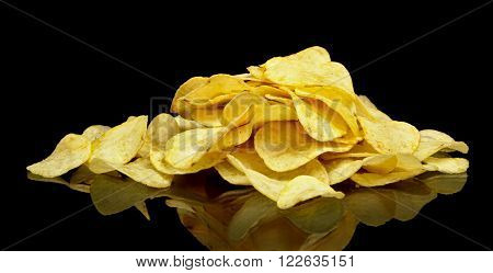 Photo of many potato chips on black background