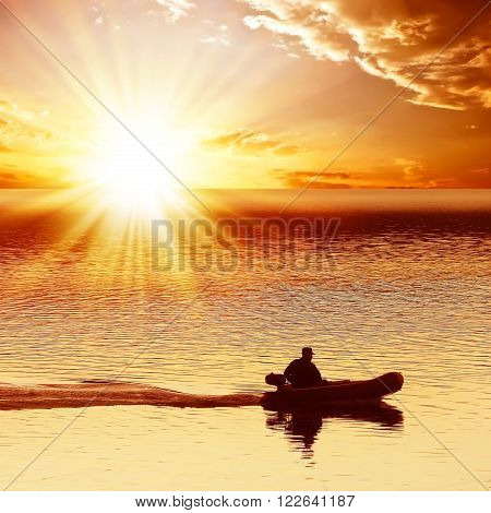 Man on a motor boat floats on the sea. On a background of a red sunset