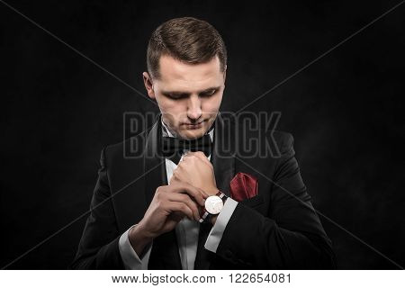 Elegant young fashion man looking at his watch over dark background.