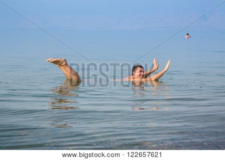 Man fooling around in the Dead Sea in Jordan. Dense salty water pushes the man out. Smiling man swims in the sea.