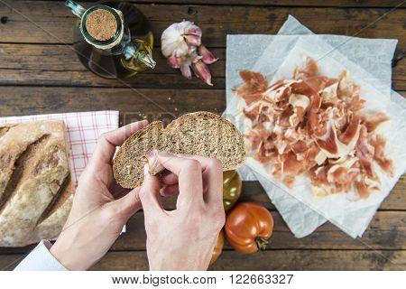 Chef rubbing garlic on a bread slice to prepare ham with garlic, tomato bread and olive oil Spanish style