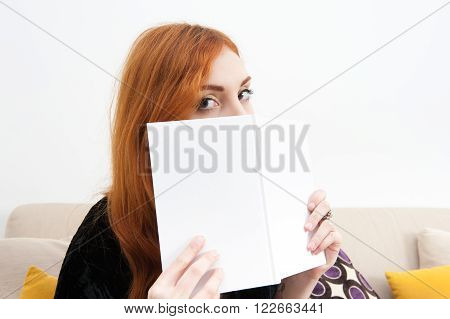 Young redhead woman at home with a book looking at camera close up