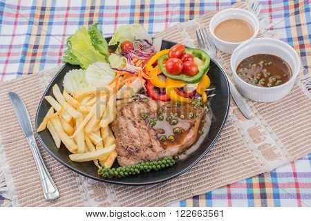 Pork steak with brown pepper sauce served with potato chips and salad with sesame japanese dressing.