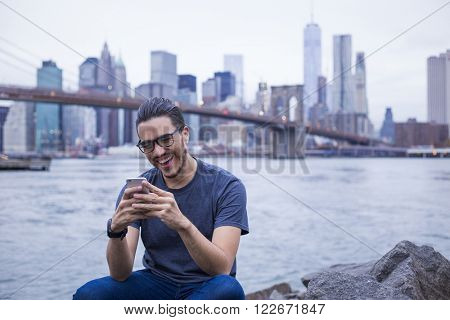 Young man texting on his smartphone in Brooklyn, New York