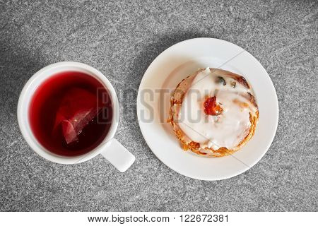 Cup of fruit tea next to belgian bun, placed on kitchen top