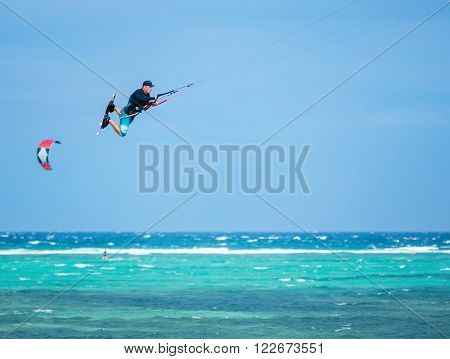 Kiteboarder performing a jump against the blue sky