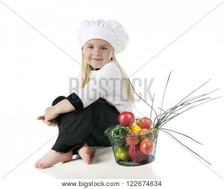 An adorable preschooler in her chef's outfit, sitting by a wire basketful of vegetables.  On a white background.