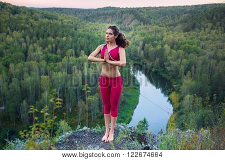 young beautiful woman doing yoga outdoors