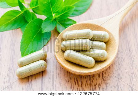 Thai herbal medicine capsules in wooden spoon with green leaves on wooden background.