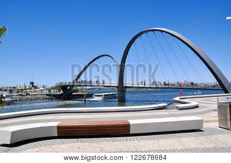 PERTH,WA,AUSTRALIA-FEBRUARY 13,2016: The modern Elizabeth Quay suspension pedestrian bridge over the artificial inlet on the Swan River with tourists and ferry underneath in Perth, Western Australia.