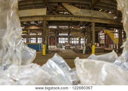 Abandoned workroom in warehouse through broken safety glass.