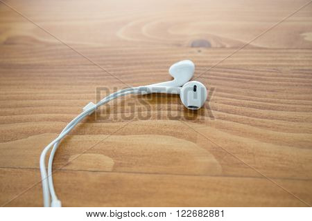white audio earphones over wooden table background