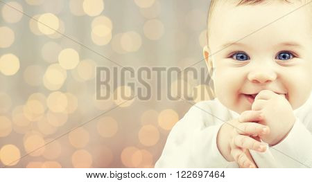 children, people, infancy and age concept - beautiful happy baby over holidays lights background