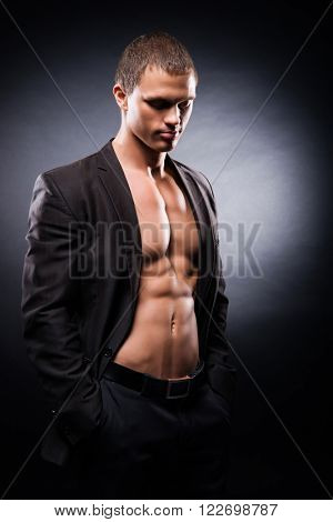 Strong, fit and sporty stripper man over black background