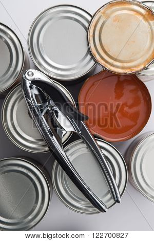 Can Opener On Tin Cans Beside Opened Can