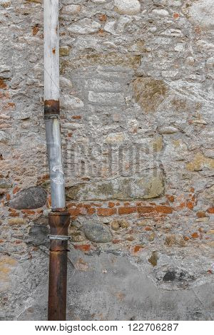 Detail of a downpipe against a brick wall.