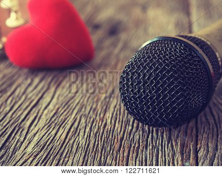Music lover concept. A Black microphone on wooden plate with red heart in out of focus background.: Vintage style and filtered process.