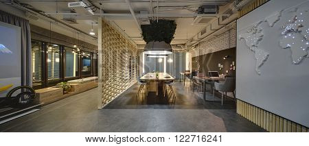Interior in a loft style. There are tables and chairs. There are notebooks, laptops, holders with pens and grass decoration on the tables. Above them hang large lamps with artificial leaves. A few laptops are on the table. On the right there is a wall wit