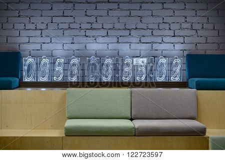 Light wooden benches with multi-colored seats on the brick wall background. Seats are made up of pillows. There is a digital clock which made from the transparent rectangles on the bench. Place for coworking.