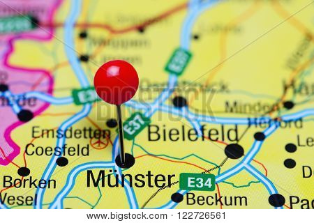 Photo of pinned Munster on a map of Germany. May be used as illustration for traveling theme.