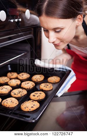 Young woman removing chocolate chip cookies from the oven in a kitchen