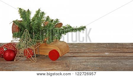 Wooden toy car with Christmas tree  and toys on a table over white background