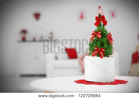 Small decorated Christmas tree on the table in the room, close up