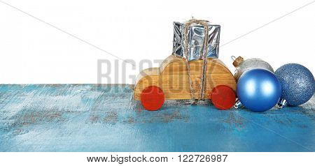 Wooden toy car with gift box and baubles on a table over white background