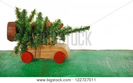 Wooden toy car with Christmas tree on a table over white background