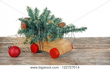 Wooden toy car with Christmas tree and bauble on a table over white background