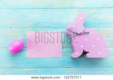 Easter egg with greeting card and rabbit on blue wooden background