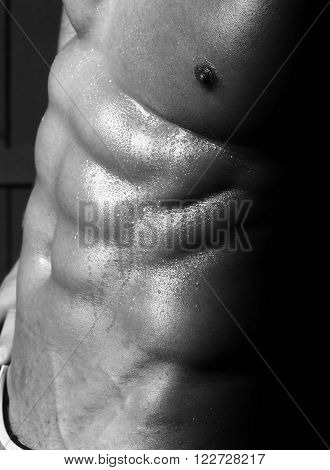Sexual male naked muscular torso with perfect six pack abdominal pectoral muscles covered with drops sporting body of sweat black and white
