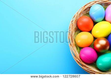 Easter eggs in nest on blue background