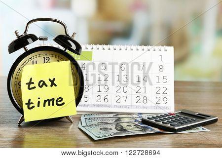 Tax time on alarm clock with dollars, calculator and calendar