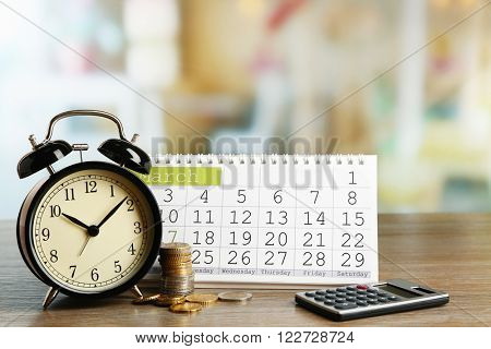 Tax time and alarm clock with coins, calculator and calendar