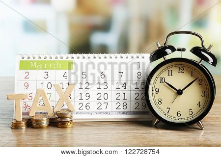 Tax time and alarm clock with coins and calendar