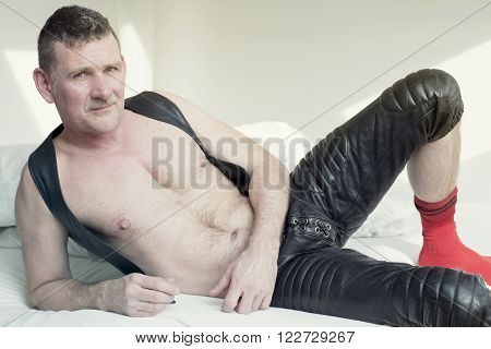 man in black fetish leather gear lying in bed and looking at camera
