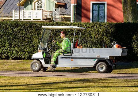 Kalmar Sweden - March 17 2016: Male worker in greenish yellow work clothes drive by in a zero emission vehicle an electric Club car Carryall 6. Real people in everyday life.