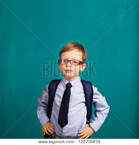 School kid rucksack. little Boy in eyeglasses. Cheerful smiling little kid with big backpack against chalkboard. Looking at camera. School concept. Back to School poster
