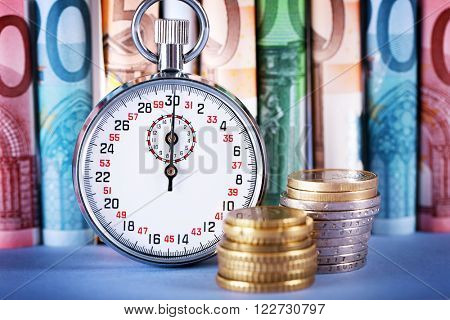 Stopwatch with twisted euro banknotes and coins on blue background. Time is money concept