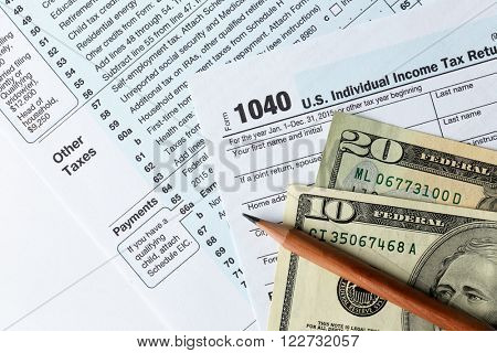 1040 Individual Income Tax Return Form for 2015 year with a pencil to fill in and dollar bills on the white desk, close up