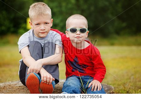 Two little sibling boys hugging and having outdoors. Brothers and best friends. Friends hugging.