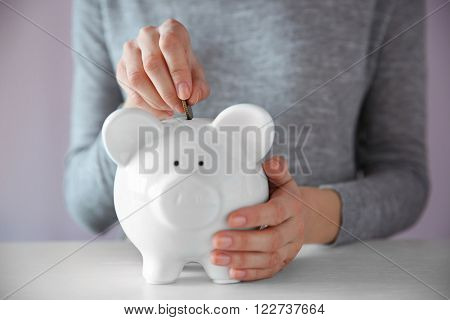 Woman putting coin into white piggy bank at the table