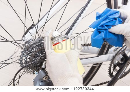 Preparing bicycle for a new season. Hands with cloth and cleaning or lubricant spray