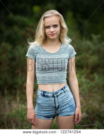 Outdoor natural light portrait of a beautiful teenage blond girl standing in the forest wearing shorts and showing belly button.
