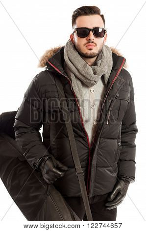 Man wearing winter clothes and sun glasses ready to travel