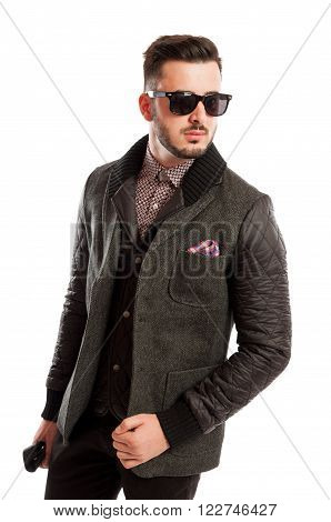 Fashionable male model wearing a cool jacket and sun glasses on white studio background