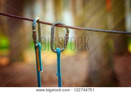 Climbing Sports Image Of A Carabiner On A Metal Rope In A Forest.